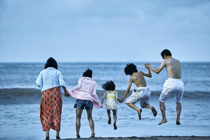 Photo tirée d'Une affaire de famille de Hirokazu Kore-eda, sur laquelle cinq membres de la petite famille sautent tous ensemble, main dans la main, face à la mer. La photo les présente de dos.
