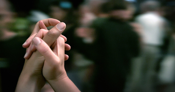 Image tirée du documentaire Le Grand Bal, sur laquelle deux mains se croisent sur une scène de danse. On sent que la caméra virevolte.