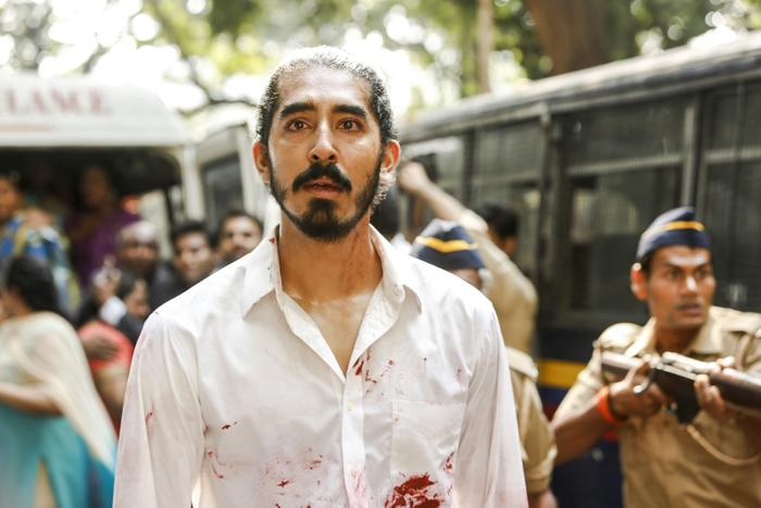 Photo de Dev Patel dans Attaque à Mumbai, sur laquelle on le voit marcher, visiblement bouleversé, dans une rue de Bombay quadrillée par les autorités. Sa chemise est tâchée de sang.