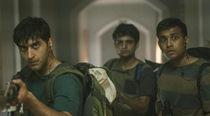 Photo tirée du film Attaque à Mumbai, sur laquelle on voit trois terroristes avancer dans l'un des couloirs de l'hôtel Taj Mahal.