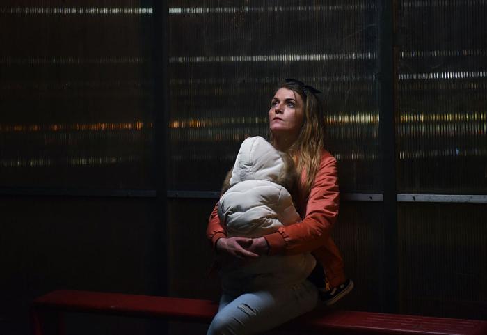 Photo tirée du film Dirty God, sur laquelle l'héroïne incarnée par Vicky Knight porte son bébé à un arrêt de bus.