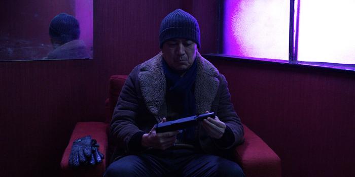 """Photo tirée du film """"Face à la nuit"""", sur laquelle le héros incarné par Jack Kao tient une arme dotée d'un silencieux."""
