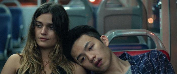 """Photo tirée du film """"Face à la nuit"""", sur laquelle les personnages incarnés par Louise Grinberg et Lee Hong-Chi sont assis côte à côte dans un bus."""