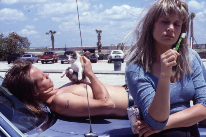 """Photo tirée de """"River of Grass"""" de Kelly Reichardt, sur laquelle les deux personnages principaux, Lee et Cozy, sont respectivement allongés et adossés sur leur voiture."""