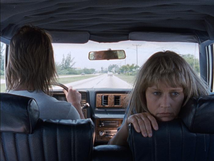 """Photo tirée de """"River of Grass"""" de Kelly Reichardt, sur laquelle les deux personnages principaux sont en voiture. Lee est au volant, tandis que Cozy regarde la banquette arrière, d'où est prise la photo."""