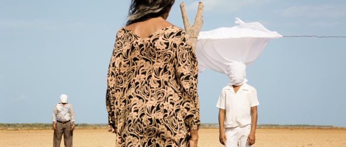 Photo tirée des Oiseaux de passage sur laquelle une femme vue de dos dans le désert observe deux hommes aux visages masqués par des linges blancs.