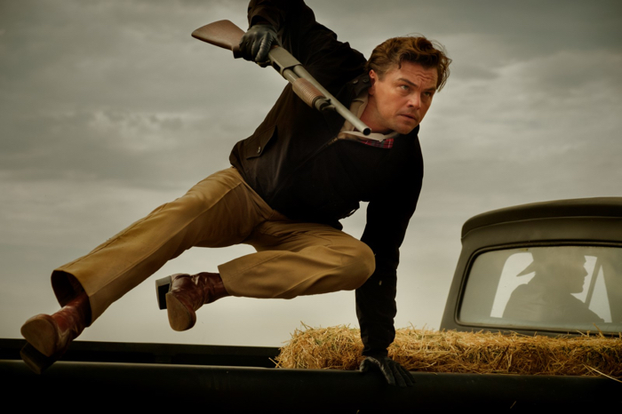 Photo de Leonardo DiCaprio dans Once Upon a Time... in Hollywood, sur laquelle il saute de l'arrière d'un pick-up, fusil à pompe en main.