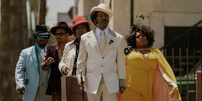 """Photo tirée de """"Dolemite Is My Name """", sur laquelle le personnage incarné par Eddie Murphy avancent fièrement dans les rues de Los Angeles."""