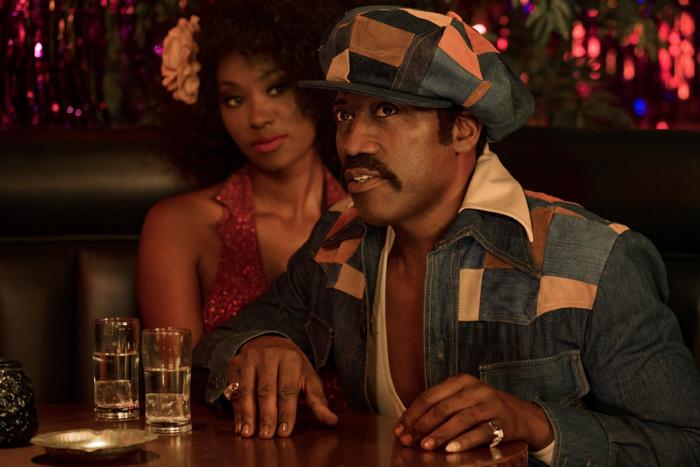 """Photo tirée de """"Dolemite Is My Name"""", sur laquelle D'Urville Martin, incarné par Wesley Snipes, est assis à la table d'un strip club en compagnie d'une jeune femme."""