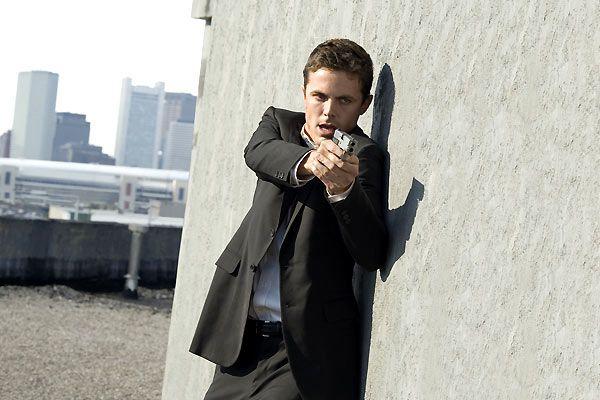 Photo de Casey Affleck dans Gone Baby Gone sur laquelle l'acteur pointe son arme sur un autre personnage sur le toit d'un immeuble.