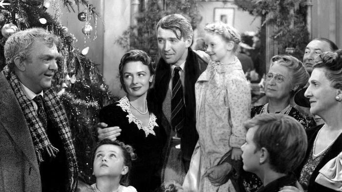 Photo de James Stewart et Donna Reed regroupés avec leur famille au pied du sapin de Noël dans le film Frank Capra.