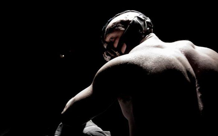 Première photo de Bane dans The Dark Knight Rises. Un oeil de chat est visible au second plan dans le noir.