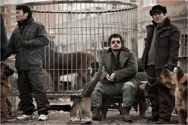 Photo tirée du film The Murderer sur laquelle nous voyons trois hommes dans un camp où des chiens sont dans des cages.