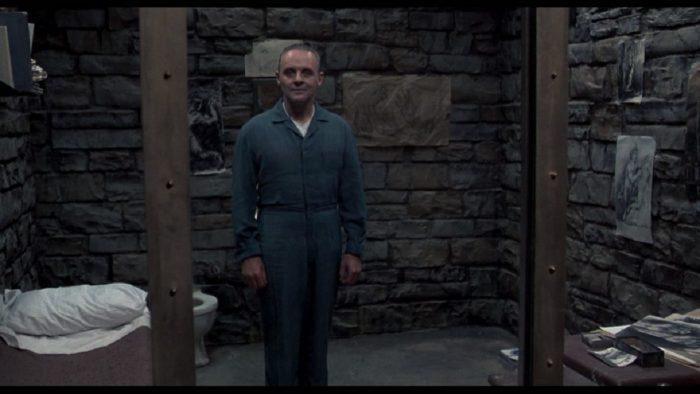 Photo d'Anthony Hopkins se tenant debout dans sa cellule dans le film Le silence des agneaux de Jonathan Demme.