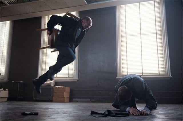 Photo de Jason Statham sautant sur un ennemi alors qu'il est attaché à une chaise dans le film Killer Elite.