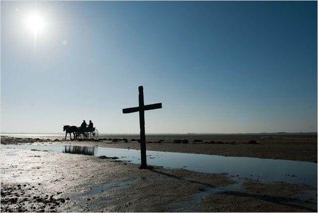 Photo tirée du film La dame en noir sur laquelle une charrette passe au milieu d'une route boueuse sur laquelle est plantée une croix.