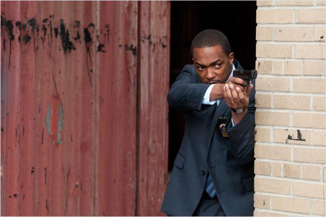 Photo d'Anthony Mackie armé et se protégeant d'un ennemi dans le film Dos au mur.
