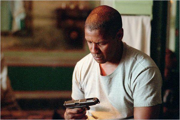 Photo de Denzel Washington observant une arme qu'il tient avec désespoir dans le film Man On Fire de Tony Scott.