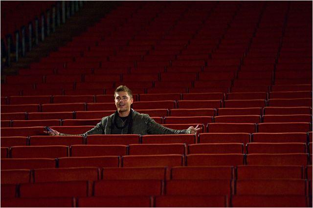 Photo de Zac Efron assis seul dans une salle de spectacle dans le film Happy New Year.
