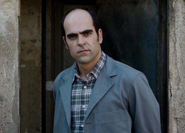 Photo de Luis Tosar face à l'objectif dans le film Malveillance. L'acteur, à l'entrée d'un immeuble, semble regarder un autre protagoniste.