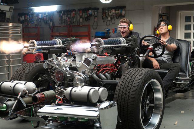 Photo de Seth Rogen et Jay Chou dans le film The Green Hornet de Michel Gondry. Les deux sont dans un prototype de voiture et tirent à la mitrailleuse.