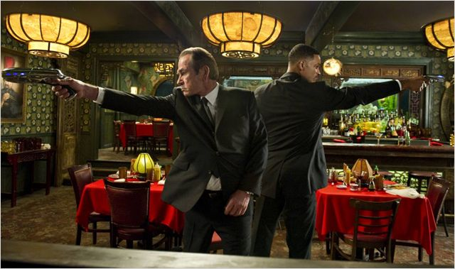 Photo de Tommy Lee Jones et Will Smith côte à côte combattant des aliens dans un restaurant chinois dans le film Men in Black 3.