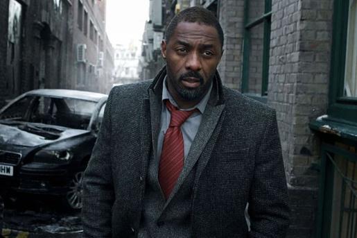 Photo d'Idris Elba avançant dans une ruelle londonienne dans la série Luther. La voiture au second plan semble ravagée.