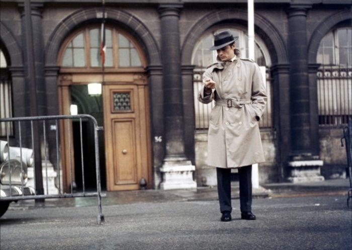 Photo d'Alain Delon dans le film Le Samouraï de Jean-Pierre Melville. Dans une rue parisienne, l'acteur regarde sa montre.