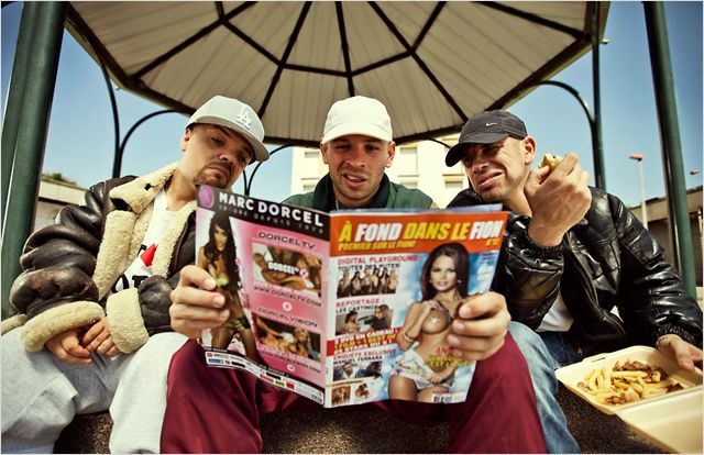 Photo du film Les Kaïra sur laquelle les trois héros lisent un magazine porno ensemble sur un banc.