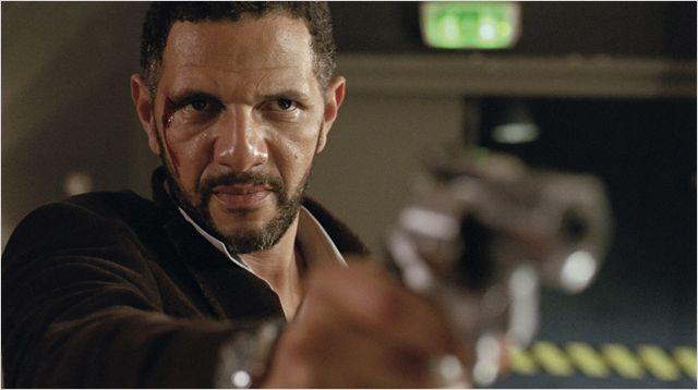 Photo de Roschdy Zem dans le film Mains Armées. Le visage ensanglanté, l'acteur pointe une arme vers une personne qu'on ne voit pas.