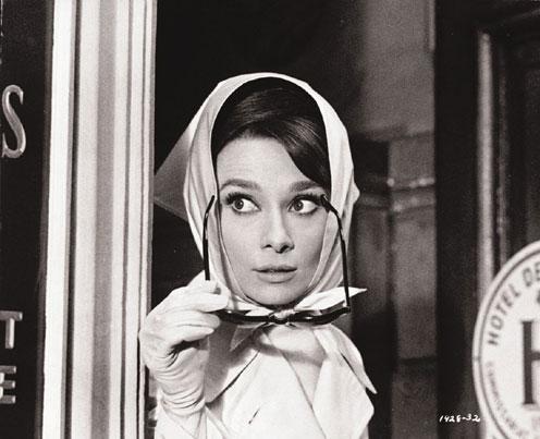 Photo d'Audrey Hepburn dans le film Charade de Stanley Donen. L'actrice sort d'un magasin et enfile des lunettes de soleil comme pour passer inaperçue.