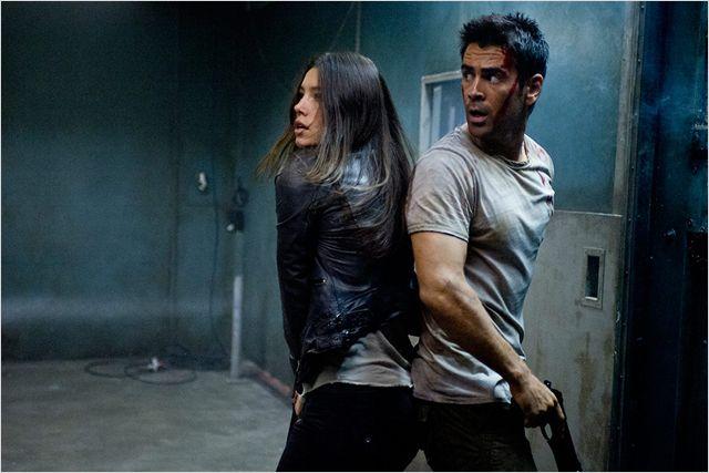 Photo de Colin Farrell et Jessica Biel dans le film Total Recall : Mémoires Programmées de Len Wiseman. Pris au piège, Farrell et Biel sont dos à dos, armés et en panique.