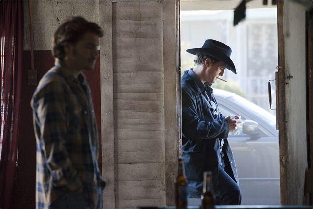 Photo d'Emile Hirsch et Matthew McConaughey dans le film Killer Joe de William Friedkin. Hirsch est à l'intérieur d'une grande alors que McConaughey est à l'extérieur près de l'entrée et allume une cigarette.