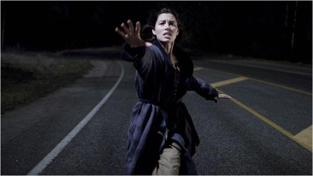 Photo de Jessica Biel dans le film The Secret. L'actrice court sur la route derrière un véhicule qu'elle tente de rattraper et vers lequel elle a la main tendue.