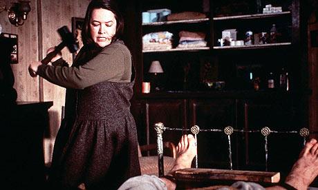 Photo de Kathy Bates dans le film Misery de Rob Reiner qui s'apprête à briser la jambe de James Caan allongé sur un lit avec une masse.