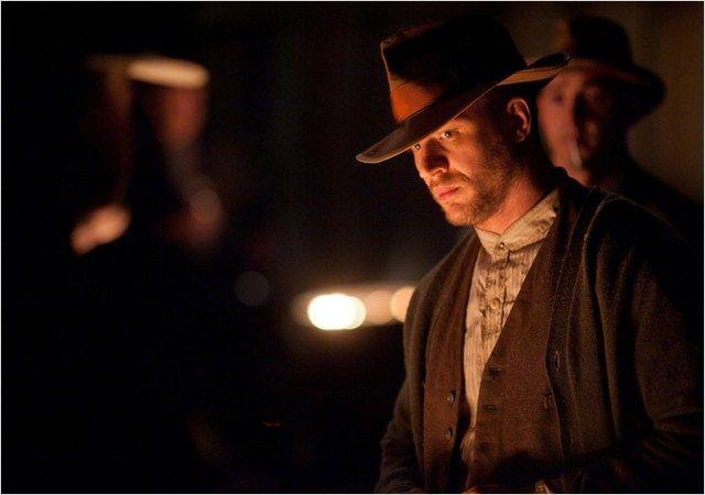 Photo de Tom Hardy dans le film Des Hommes sans Loi de John Hillcoat. L'homme se tient debout près d'un feu entouré d'autres hommes.