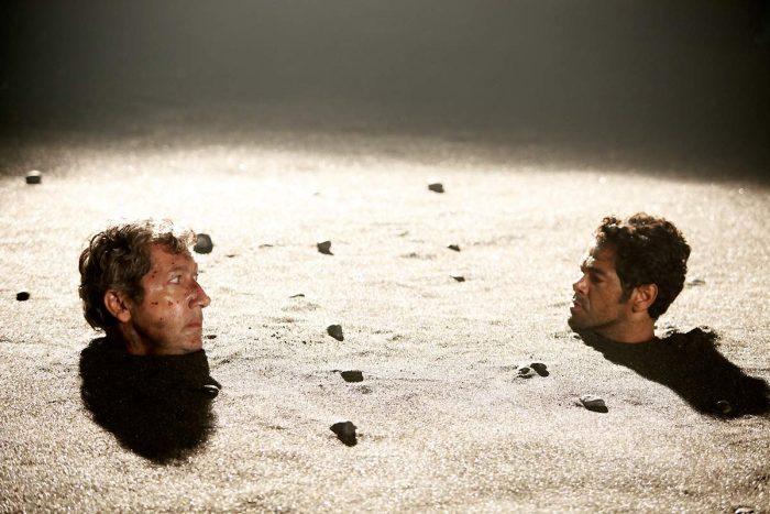 Photo d'Alain Chabat et Jamel Debbouze dans le film Sur la piste du Marsupilami d'Alain Chabat. Les deux acteurs sont enterrés dans le sable. Leur tête ressort et ils se regardent avec un air colérique.