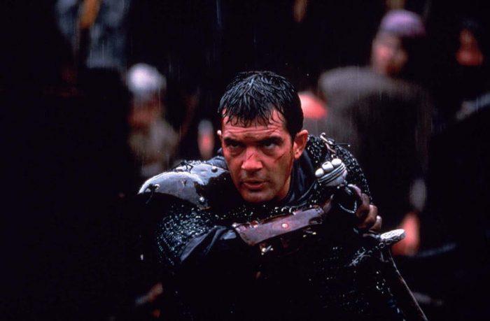 Photo d'Antonio Banderas durant la bataille finale du film Le 13ème Guerrier de John McTiernan. L'acteur s'empare de son épée sous la pluie.