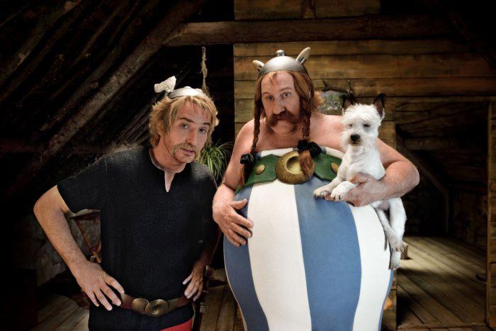Photo d'Edouard Baer et Gérard Depardieu dans Astérix et Obélix : Au Service de Sa Majesté. Les deux héros sont dans une demeure en bois et regardent avec interrogation un troisième protagoniste.