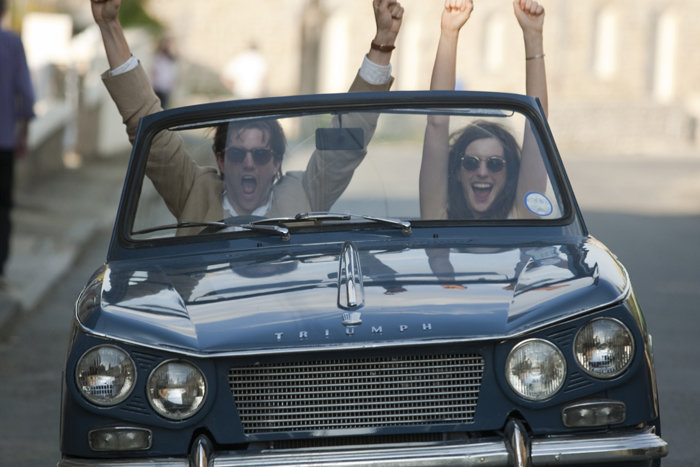 Photo de Jim Sturgess et Anne Hathaway dans le film Un jour. En voiture décapotable, les deux acteurs crient de joie et lèvent leurs bras en l'air.