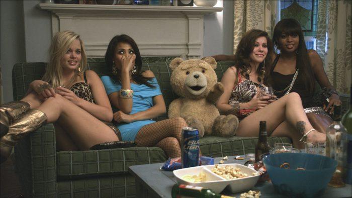 Photo de l'ours Ted dans le premier volet de ses aventures réalisé par Seth MacFarlane. L'ourson est assis dans un canapé entouré de call-girls avec des boissons et à manger sur la table basse délaissée.