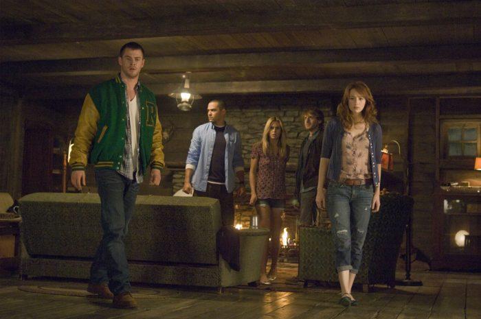 Photo de Chris Hemsworth dans le film La Cabane dans les bois de Drew Goddard. Chris Hemsworth et ses amis semblent s'avancer vers une trappe avec un air inquiet.