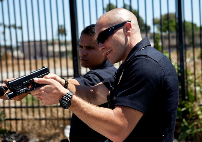 Photo de Jake Gyllenhaal et Michael Peña dans le film End Of Watch. En tenue de policiers, les deux acteurs semblent effectuer un contrôle de véhicule. Gyllenhaal pointe son arme vers la voiture que l'on ne distingue pas.