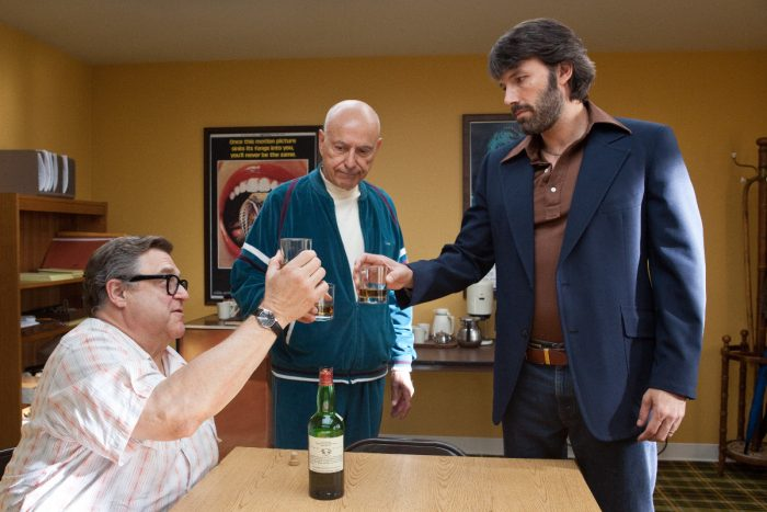 Photo de John Goodman, Alan Arkin et Ben Affleck dans le film Argo. Les trois personnages trinquent avec un verre de whisky dans un appartement.