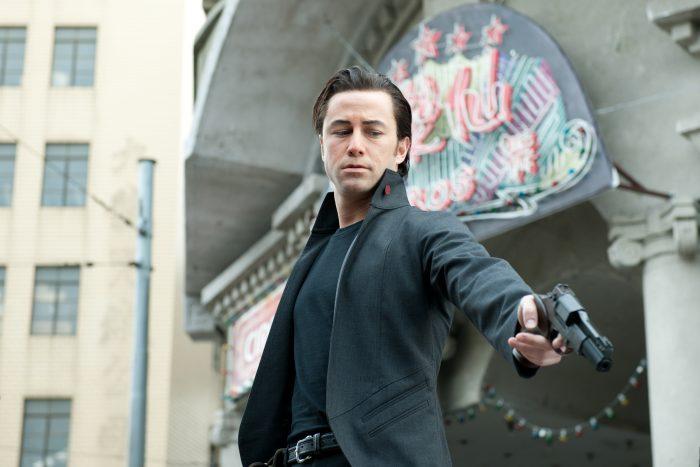 Photo de Joseph Gordon-Levitt dans Looper de Rian Johnson où l'acteur pointe une arme vers une victime au sol.