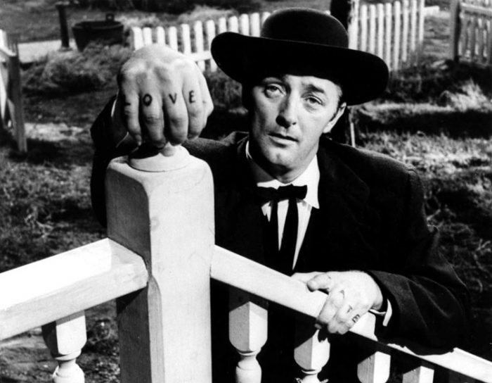 Photo mythique de Robert Mitchum dans le film La Nuit du Chasseur de Charles Laughton. L'acteur est en bas du perron d'une maison et pose sa main sur la colonne d'un escalier. Le mot Love est tatoué sur sa main droite et l'on devine le mot Hate sur sa main gauche.