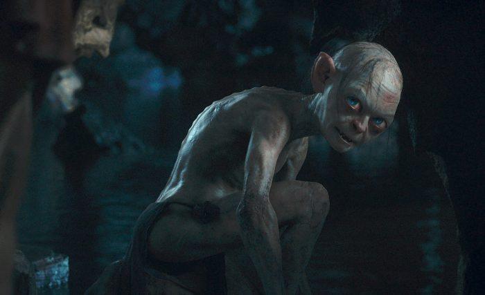 Photo d'Andy Serkis dans le rôle de Gollum dans le film Le Hobbit : Un voyage inattendu. L'acteur est face à Bilbon qu'on ne voit pas et le regarde avec un air noir, accroupi dans sa grotte.