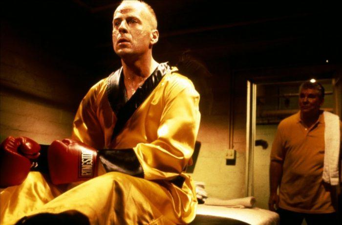 Photo de Bruce Willis dans le film Pulp Fiction de Tarantino qui se réveille brutalement d'un rêve dans un gymnase avant un combat de boxe.