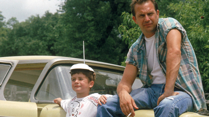 Photo de Kevin Costner et T.J. Lowther dans le film Un Monde Parfait de Clint Eastwood. Les deux personnages sont assis et adossés à une voiture en pleine campagne.