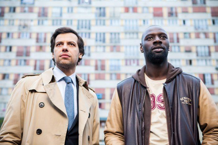 Photo d'Omar Sy et Laurent Lafitte dans le film De l'autre côté du périph. Les deux acteurs sont face à l'objectif devant un très grand immeuble de la région parisienne.